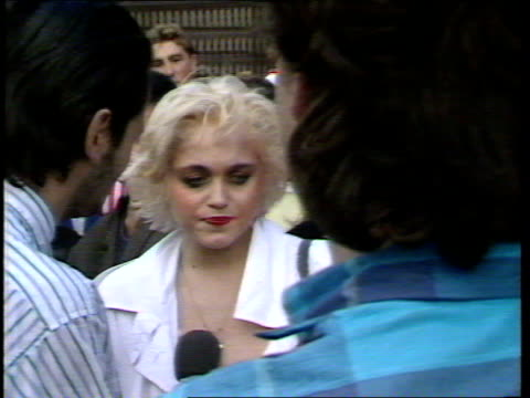 madonna at wembley; england: london: wembley: ext cms madonna lookalike chatting press pull out tms crowds walking into stadium towards two girls... - マドンナ点の映像素材/bロール