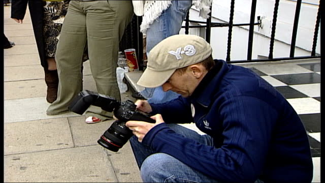 madonna speaks out about adopting malawi orphan ext two women admiring photograph on digital camera press waiting outside madonna's house low angle... - digital camera stock videos and b-roll footage