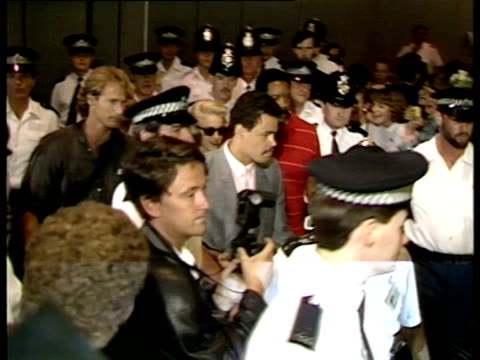 vídeos y material grabado en eventos de stock de madonna walking through heathrow airport surrounded by police and photographers after arriving for british tour on august 13 1987 / london england /... - rodear