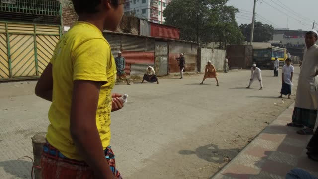 vídeos de stock, filmes e b-roll de madrasa student play cricket on street at the bank of the buriganga river in dhaka bangladesh on march 19 2018 the chemical waste of mills and... - madressa