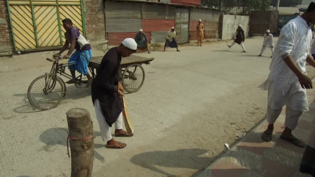 madrasa student play cricket on street at the bank of the buriganga river in dhaka bangladesh on march 19 2018 the chemical waste of mills and... - madressa stock videos and b-roll footage