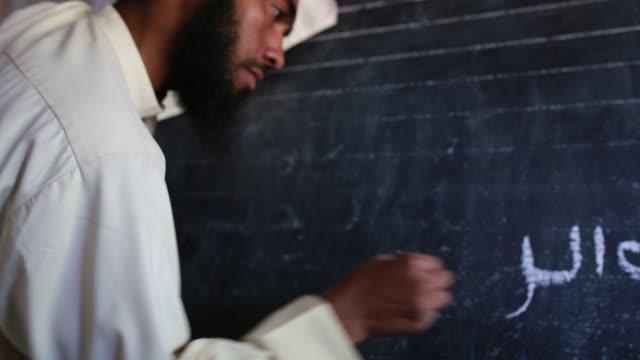 vidéos et rushes de madrasha teacher write arabic language on blackboard to teach the students at barguna near sundarban, bangladesh, on january 21, 2018. the... - gomme