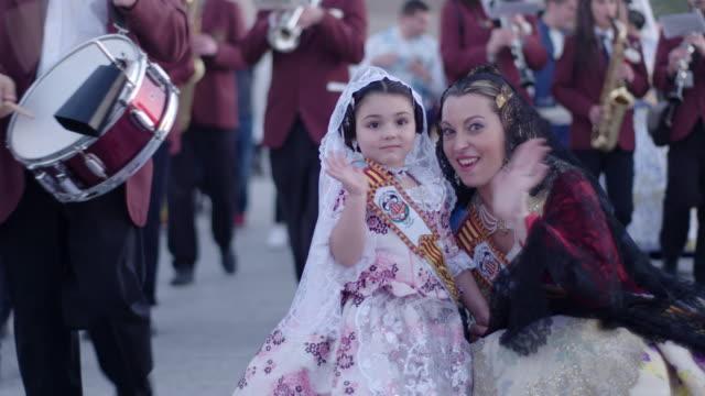 Madre e hija vestidas de falleras saludan a la cámara