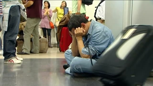 vídeos de stock, filmes e b-roll de madrid airport int exhausted returning traveller seated crosslegged on floor with his head resting in his hands returning air passenger fanning... - cross legged