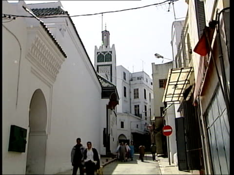 Moroccans named as suspects ITN MOROCCO Tangiers People along narrow street LA MS Building overhanging the street TILT DOWN people in street BV...