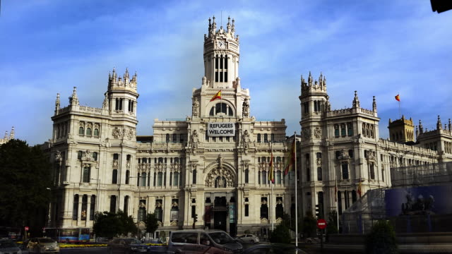 madrid city hall cibeles palace with welcome refugees flag in the front timelapse