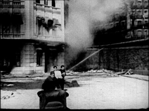 Madrid under seige / troops standing by cannon firing / Italian bomber airplanes in air / men moving belongings from burning buildings / men carrying...