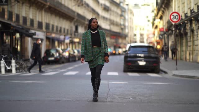 magalie kab wears a black wool turtleneck pullover, a golden necklace, a green and red checked blazer jacket with printed houndstooth patterns, a... - black colour stock videos & royalty-free footage