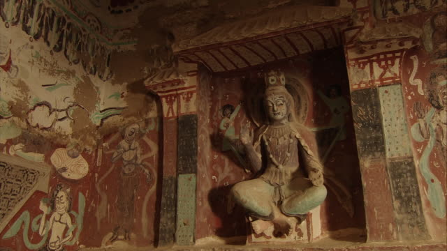 vídeos de stock e filmes b-roll de magao caves; south district; the 275th cave; buddha statue and murals - cross legged