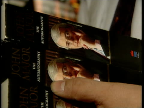 magazine considers legal action; itn ???: bookshop worker putting copies of major's autobiography on shelf iain dale interviewed sot - we've had lot... - 伝記点の映像素材/bロール