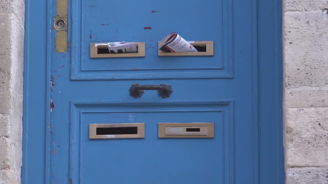 magazines in a mailboxes at a blue old door