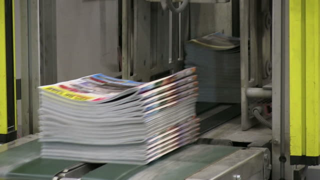 cu magazines passing on conveyor belt in gravure printing office / itzehoe, schleswig-holstein, germany  - zeitschrift stock-videos und b-roll-filmmaterial