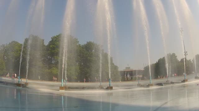 magestic fountains shoot water in air with runners in background - unisphere stock videos & royalty-free footage