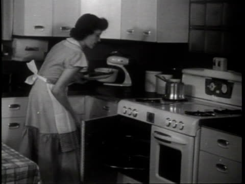 magic chef inc in st louis missouri celebrates it's 50th anniversary by making more gas ranges / woman in apron stirs pot and removes roast from oven... - roast dinner stock videos & royalty-free footage