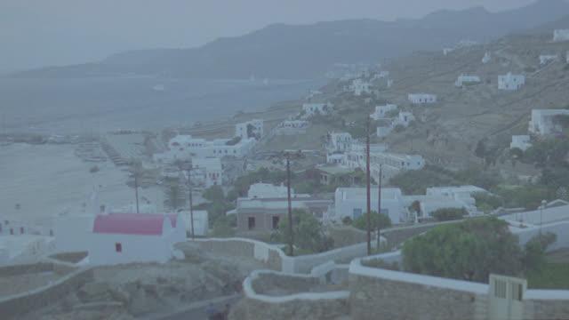 magic hour greek coastal village; camera pans r to l - greece stock videos & royalty-free footage