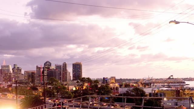 magic hour skyline of downtown San Diego and traffic on Interstate 5 as seen from residential street in the hills above the city