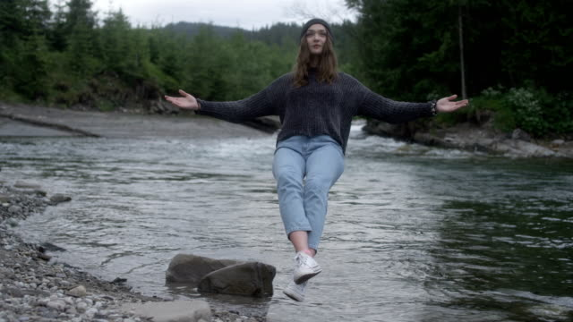 magic in nature. woman levitating above the stream - arms outstretched stock videos and b-roll footage