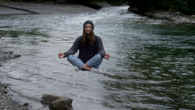 magic in nature. woman levitating above the stream - levitation stock videos & royalty-free footage