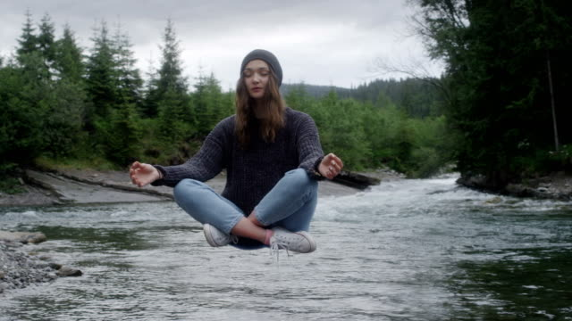 magic in nature. woman levitating above the stream - woman sitting cross legged stock videos & royalty-free footage