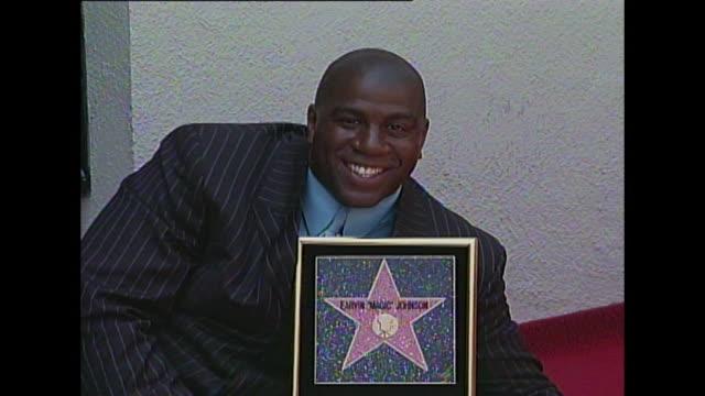 magic johnson at his star on the hollywood walk of fame - マジック・ジョンソン点の映像素材/bロール