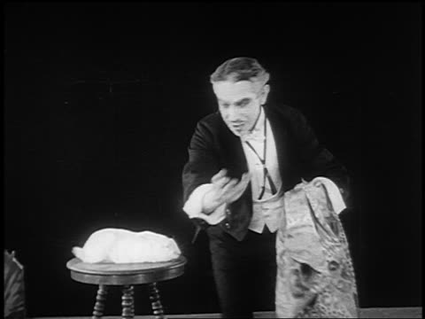 vídeos de stock, filmes e b-roll de b/w 1922 magician (ernie adams) holds cloth over rabbit on stool, removes cloth to reveal chicken - mágico