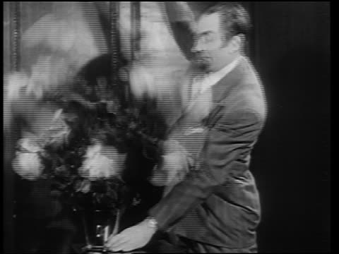 vídeos de stock, filmes e b-roll de b/w 1946 magician in suit pulling tube to reveal large bouquet of flowers - mágico