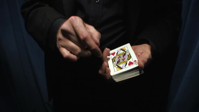 vídeos de stock, filmes e b-roll de magician performing magic card trick - mágico