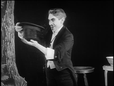 vídeos de stock, filmes e b-roll de b/w 1922 magician pulling rabbit out of top hat on stage - chapéu