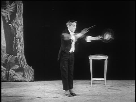 vídeos de stock, filmes e b-roll de b/w 1922 magician tapping top hat with wand on stage - mágico