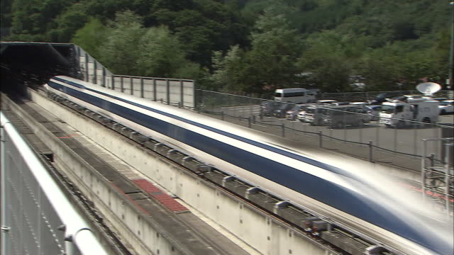 vidéos et rushes de a maglev train speeds out of a tunnel and past photographers on a trial run - préfecture de yamanashi