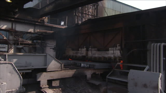 a magnetic crane hoists a steel bar across a steel yard and onto a conveyor. - hoisting stock videos & royalty-free footage