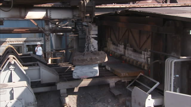 a magnetic crane hoists a steel bar. - hoisting stock videos & royalty-free footage