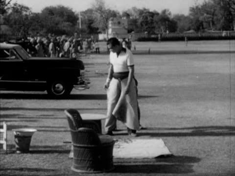 Maharaja Sawai Man Singh II being help w/ chaps WS People sitting in outdoor chairs VS Maharaja on polo pony MS Bugler in uniform VS Polo match...