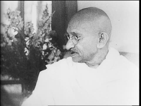 mahatma gandhi exiting a car / gandhi seated speaking with sir stafford cripps / crowded street in india / indian troops marching in line / view of... - marciare video stock e b–roll