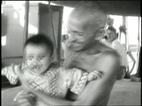 stockvideo's en b-roll-footage met mahatma gandhi laughs as he holds a baby girl. - mahatma gandhi