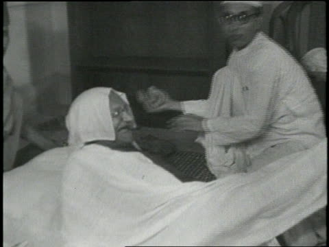 stockvideo's en b-roll-footage met mahatma gandhi lies down on the floor during his hunger strike. - mahatma gandhi