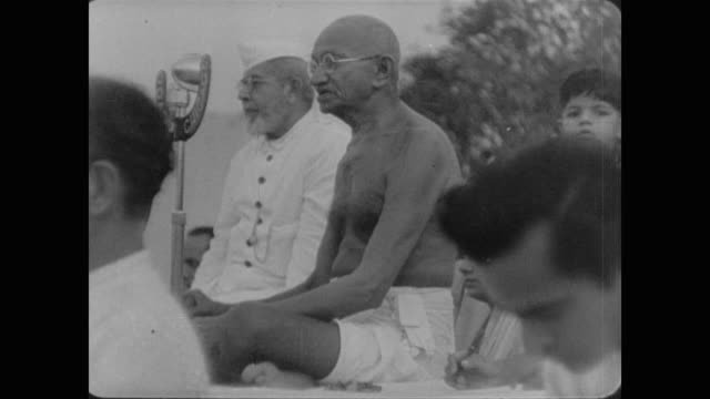 stockvideo's en b-roll-footage met mahatma gandhi sits cross legged and bare chested in front of large crowd of untouchables and followers before being helped into his bed - mahatma gandhi