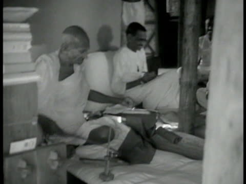 stockvideo's en b-roll-footage met mahatma gandhi sitting, making thread. other indian men turning spinning wheels. gandhi walking w/ group under umbrella. gandhi & group walking by.... - mahatma gandhi