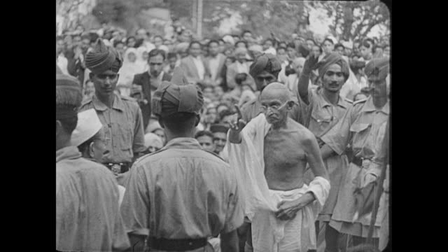 "stockvideo's en b-roll-footage met mahatma gandhi walks passed an agitated crowd as a voice over states: ""arbitration of india's political problems still remain unsolved"" - mahatma gandhi"