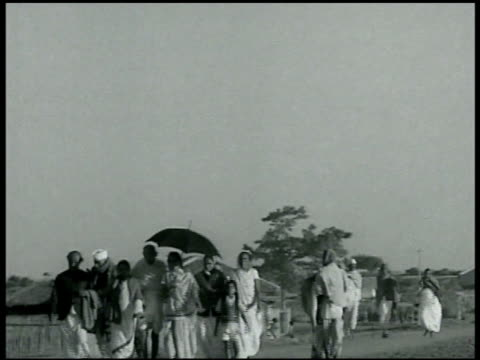 stockvideo's en b-roll-footage met mahatma [mohandas karamchand] gandhi walking w/ small entourage, woman holding umbrella over gandhi while walking, gandhi holding her shoulder as... - mahatma gandhi