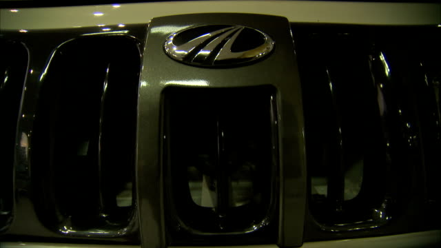 A Mahindra hood emblem shines on the grille of a vehicle at a car dealership in Delhi, India.