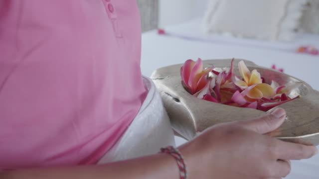 vídeos y material grabado en eventos de stock de a maid housekeeper dropping flower petals on a bed at a villa resort hotel room in exotic tropical bali, indonesia. - hospitalidad