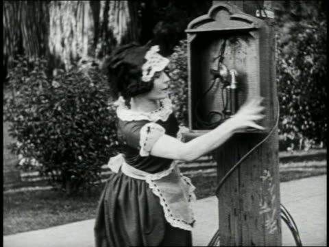 B/W 1924 maid opening patrol box + talking into old-fashioned phone / feature