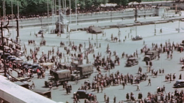 maids on balcony observing ve day celebrations in place de la concorde with the luxor obelisk fountain large crowd and french flag flying / paris... - ve day stock-videos und b-roll-filmmaterial
