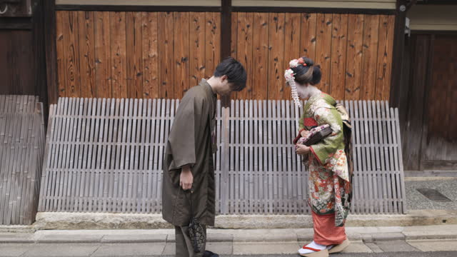 maiko (geisha in training) and a man in hakama bowing on old japanese street - tradition stock videos & royalty-free footage