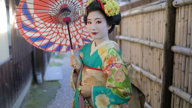 maiko apprentice geisha standing on narrow street in gion, kyoto - giappone video stock e b–roll