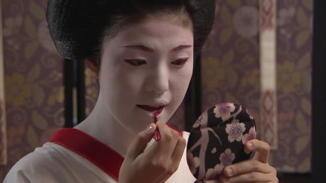 cu maiko holding hand mirror and applying lipstick, kyoto, japan - nur junge frauen stock-videos und b-roll-filmmaterial