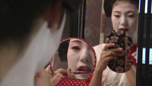 stockvideo's en b-roll-footage met cu selective focus maiko holding hand mirror and applying lipstick, kyoto, japan - make up