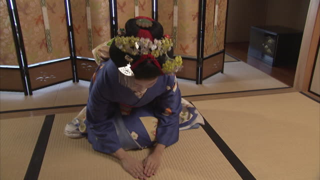 MS Maiko kneeling on mat and bowing, Kyoto, Japan