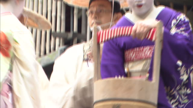 Maiko release goldfish from wooden buckets.
